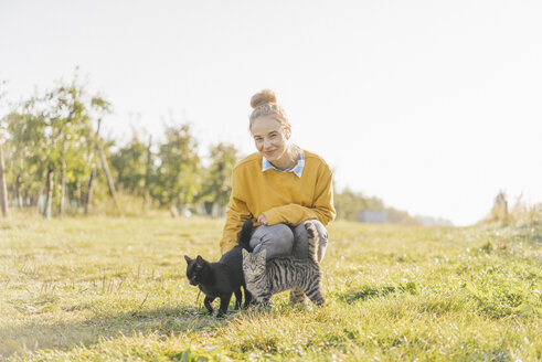 Smiling young woman with two cats on the countryside - KNSF00728