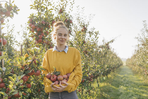 Young woman holding apples in orchard - KNSF00737