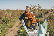 Young woman relaxing in cottage garden - KNSF00743