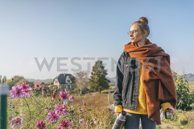 Young woman with thermos flask in cottage garden - KNSF00746