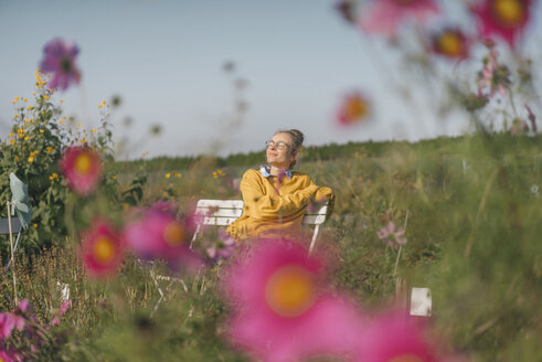 Young woman relaxing in cottage garden - KNSF00749