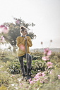 Young woman with spade in cottage garden - KNSF00755