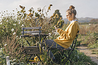 Young woman relaxing in cottage garden - KNSF00764