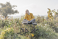 Young woman relaxing in cottage garden - KNSF00767