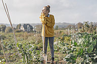 Young woman with spade in cottage garden - KNSF00776