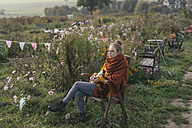 Young woman relaxing in cottage garden - KNSF00782