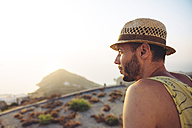 Greece, Milos, Man with straw hat looking at distance - GEMF01309