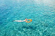 Greece, Milos, Woman floating on water - GEMF01321