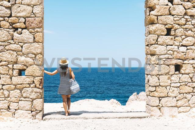Greece, Milos, Firopotamos Beach, Woman standing in door in stone wall, looking at distance - GEMF01333