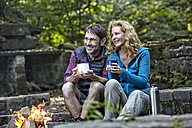 Happy couple sitting at camp fire - FMKF03318