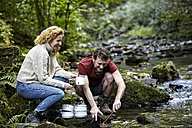 Couple washing dishes at a river - FMKF03321
