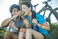 Young couple mountain biking in nature, taking a break under tree - ZEF11872