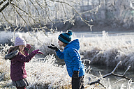 Brother and little sister playing together in winter - SARF03095