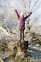 Portrait of happy girl with arms raised standing on tree trunk in winter - SARF03098