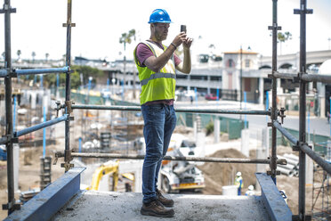 Construction worker on construction site taking pictures with smart phone - ZEF11890