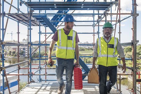 Construction workers on construction site carrying tool boxes - ZEF11899