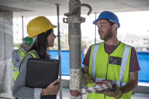 Engineer inspecting construction site, talking to workers - ZEF11902