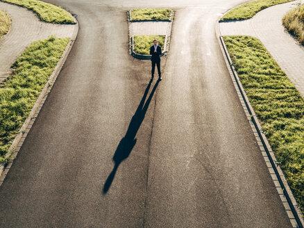 Focused businessman standing on road - KNSF00790