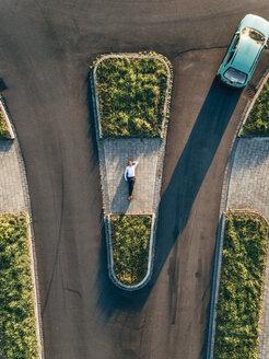 Businessman lying on traffic island - KNSF00796