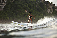 Indonesia, Bali, woman surfing - KNTF00590