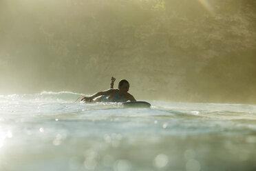Indonesia, Bali, woman lying on surfboard in the sea - KNTF00593