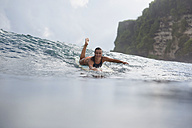 Indonesia, Bali, woman lying on surfboard in the sea - KNTF00599