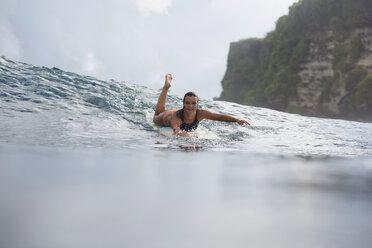 Indonesia, Bali, woman lying on surfboard in the sea - KNTF00599