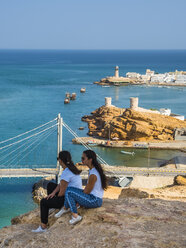 Oman, Ash Sharqiyah, Ad Daffah, back view of two women sitting on a rock in front of seaport Sur - AMF05162