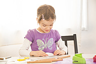 Littel girl tinkering at home, folding paper - LVF05736