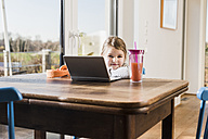 Little girl sitting at home using laptop - UUF09528