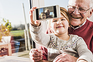 Grandfather and granddaughter taking selfies with a smart phone - UUF09546