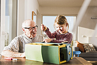 Grandfather and granddaughter assembling toy bus - UUF09549