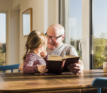 Grandfather reading out story for his granddaughter - UUF09552