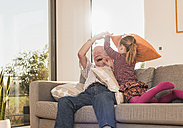 Grandfather and granddaughter having a pillow fight on couch - UUF09558