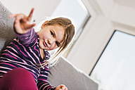 Little girl sitting on couch, making victory sign - UUF09579