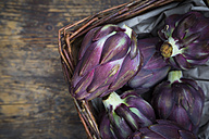 Basket of purple organic artichokes on dark wood - LVF05740