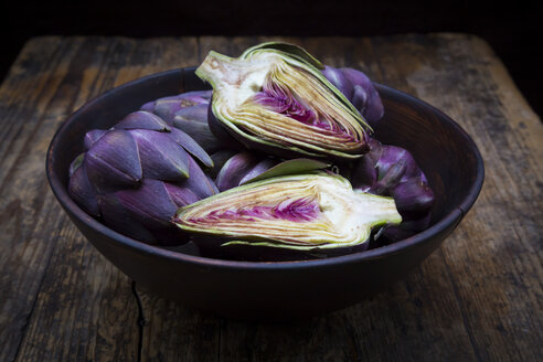 Bowl of purple organic artichokes on dark wood - LVF05746