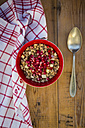 Bowl of granola with pomegranate seed and red apple on wood - LVF05748