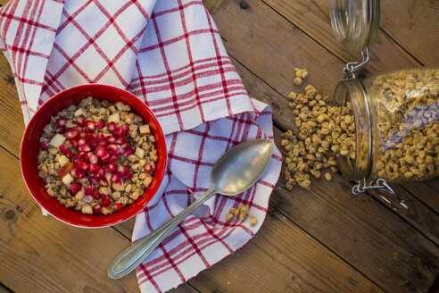 Bowl of granola with pomegranate seed and red apple on wood - LVF05751