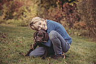 Boy hugging Labrador Retriever in garden - MFF03398