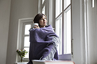 Woman wrapped in a blanket looking out of window - RBF05344