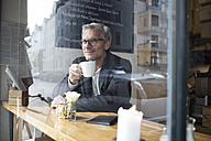Mature man drinking coffee in a cafe - RBF05362