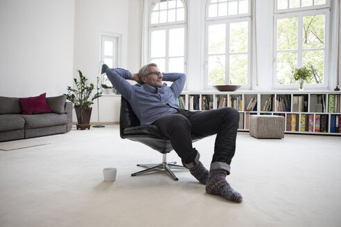 Relaxed mature man at home sitting in chair - RBF05371