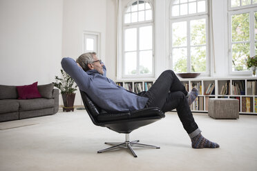 Relaxed mature man at home sitting in chair - RBF05374