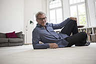 Relaxed mature man at home lying on floor - RBF05377