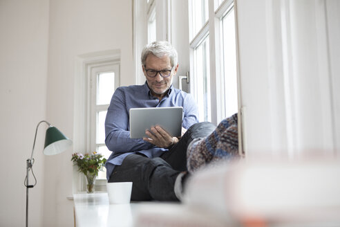 Mature man at home sitting at the window using tablet - RBF05380