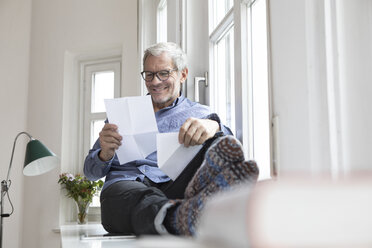Mature man at home sitting at the window reading documents - RBF05383