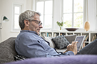 Mature man at home sitting on the sofa using tablet - RBF05389
