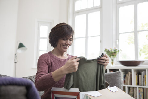 Smiling woman at home sitting on the sofa looking at garment - RBF05395