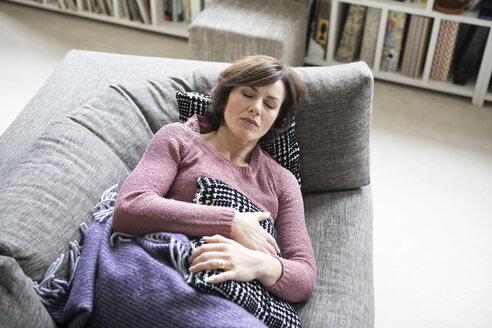Woman with stomach ache lying on the sofa - RBF05398